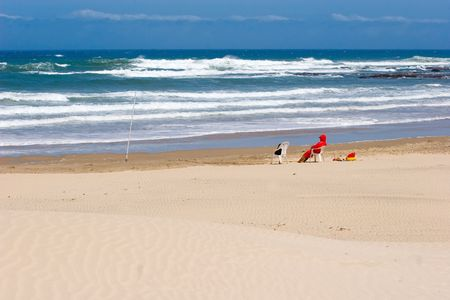 lifeguard with red jacket on-duty at an empty beach with sand,ocean and sky visible,seated on white plastic chair