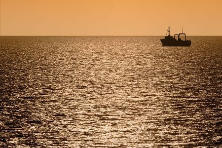 silhouette of fishing trawler at dusk sailing away with light reflecting on the ocean Stock Photo