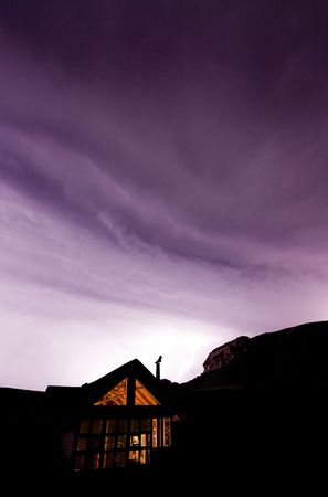 mountain cabin in foreground in thunderstorm with lightning lighting the mountain in the background