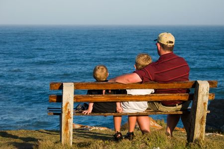 father and his two sons on a bench looking out over the ocean