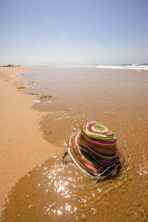 colored sun hat on water edge on deserted beach