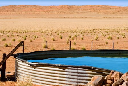 corrugated iron dam with cool blue water on desert farm