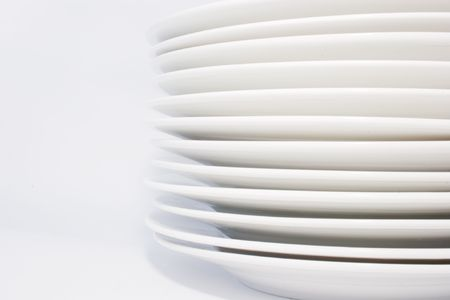 stack of white dinner plates on white background,side-view