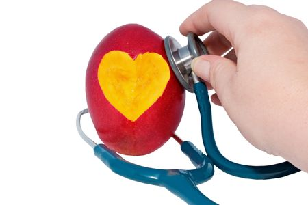 mango with heart shape cot out and hand holding a stethoscope isolated on white Standard-Bild