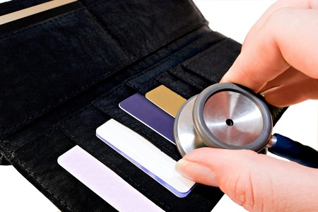 wallet with coins,notes and till slips being checked by stethoscope depicting concept of credit check or financial health Stok Fotoğraf