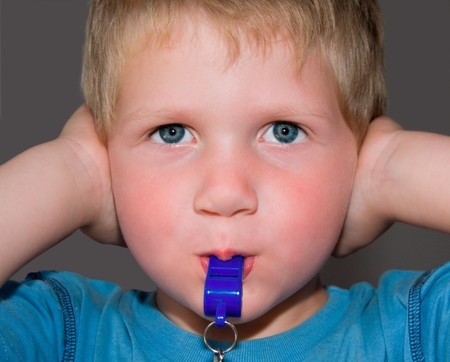 young toddler blond boy blowing blue whistle while hlding his ears shut