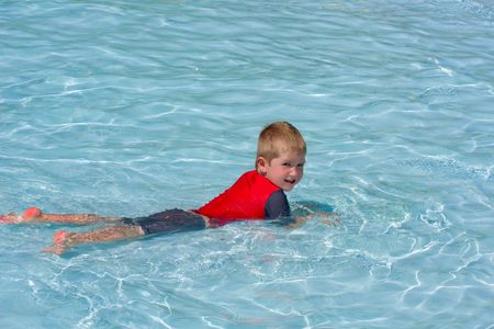 young caucasian boy with sun protection swimsuit on lying on his tummy in a pool looking at the camera
