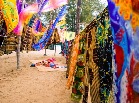 assortment of colorful sarongs strung up in informal market blowing in the wind