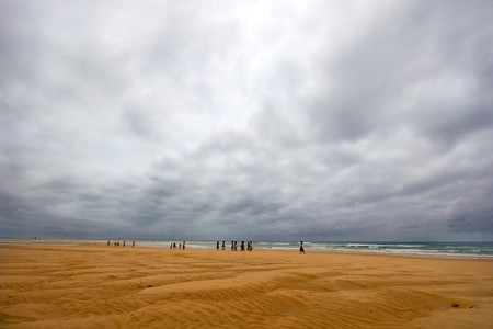 natural moody: beach with stormy skies and indigenous fishermens wives waiting for the fishing dhows to come in with the catch of the day