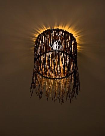 lampekap: interessante lampenkap geweven uit twijgen met glimmende gloeilamp Stockfoto