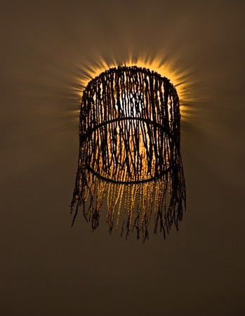 interesting lampshade woven from twigs with shining lightbulb  Stock Photo