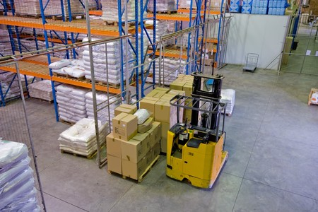 inside of commercial warehouse with goods stacked and forklift Stock Photo