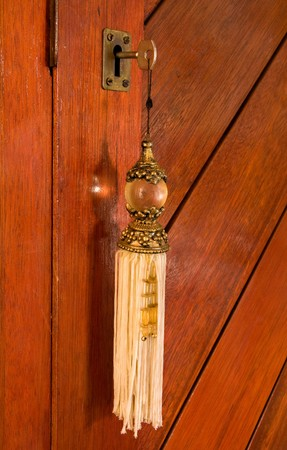 keyholder: key in a lock with a fancy and elaborate tassel key ring