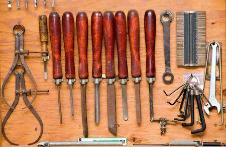 set of chisels and other tools hanging in wooden cupboard against a wall