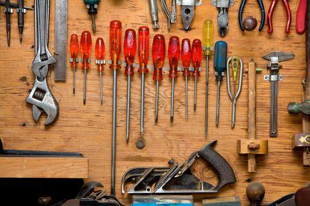 スクリュー ドライバーおよび木製の食器棚の壁にぶら下がっている他のツールのセット