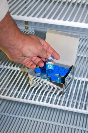 closeup of veterinarian getting a vial of medicine from a fridge