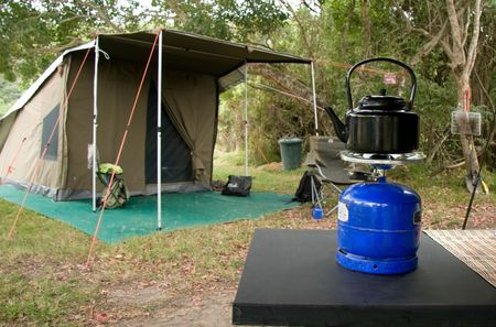 gas stove: kettle  on a burner at a campsite with tent in background Stock Photo