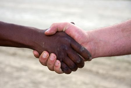 black handshake: closeup of a hand shake,interracial between black and white. Dusty,dirty hands outdoors,