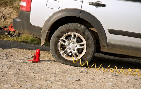 flat tyre of dusty dirty car being re-inflated by small compressor pump