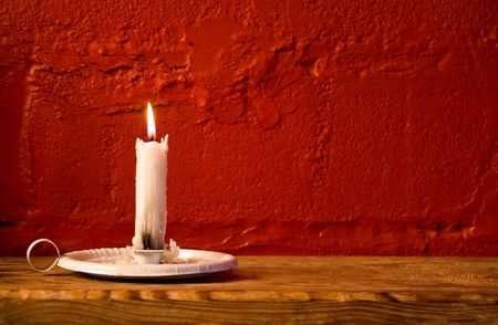 candle: burning white wax candle in old candle holder on wooden bench against red rustic wall Stock Photo