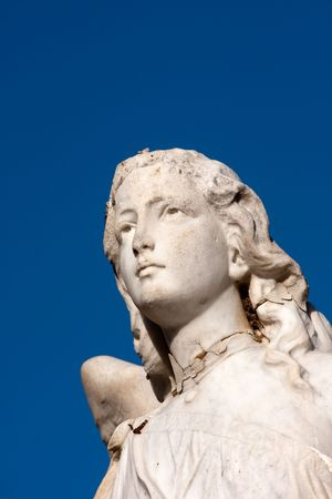 closeup of white weathered stone angel face blue sky