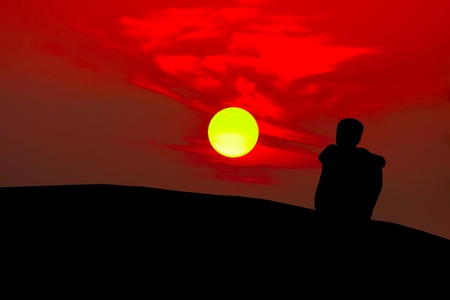 introspective: silhouette of adolescent boy sitting on mountain watching bright red yellow sun setting Stock Photo