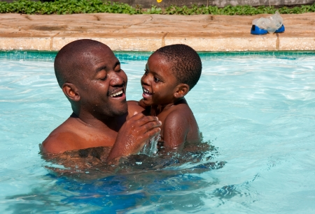 african black man and son swimming in bright sunlight in pool