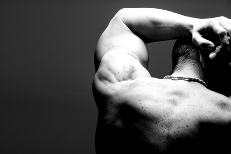 muscular male shoulder and back in black and white photo