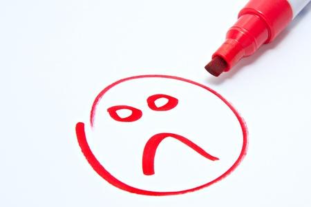 cara triste dibujado en blanco con lápiz rojo mostrando insatisfacción del cliente