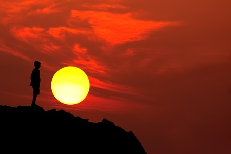 introspective: adolescent boy silhouette on mountain sunset with red sky and yellow round sun