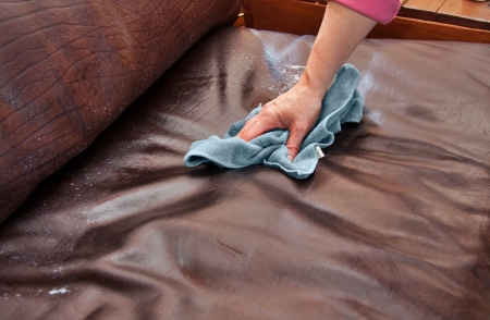 closeup of hand cleaning and conditioning a leather couch with conditioning product and blue microfiber cloth