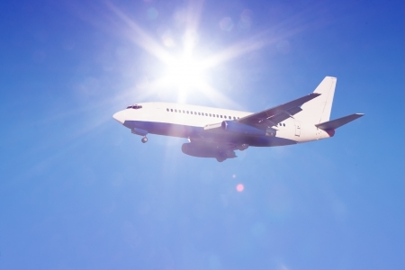 passenger jet in flight against clear blue sky with sun rays and flares landing gear down Stock Photo