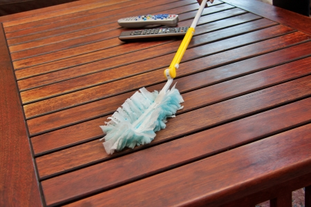 dusting a wooden coffee table with a synthetic duster, closeup perspective shot