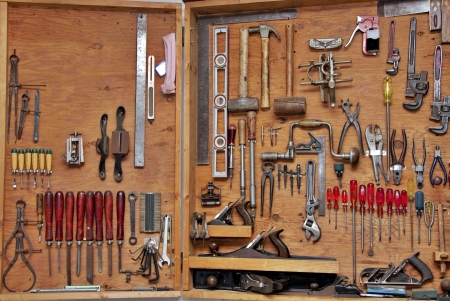 assortment of DIY tools hanging in a wooden cupboard against a wall Archivio Fotografico