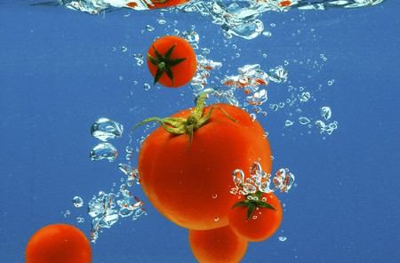 A series, vegetables in water on a dark blue background photo