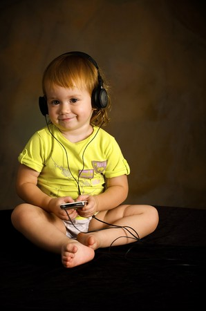 Small girl listens to the music Stock Photo