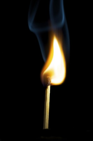 Wooden match burning on a black background