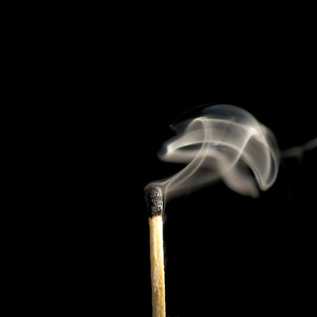 Wooden match burning on a black background photo