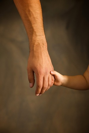 Daughter holds the hand of the father photo
