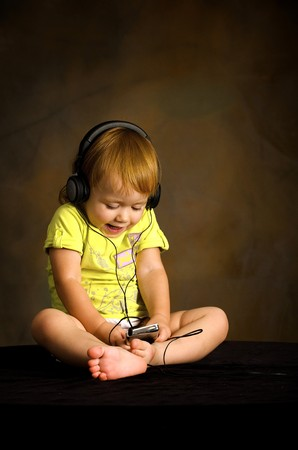 Small girl listens to the music photo