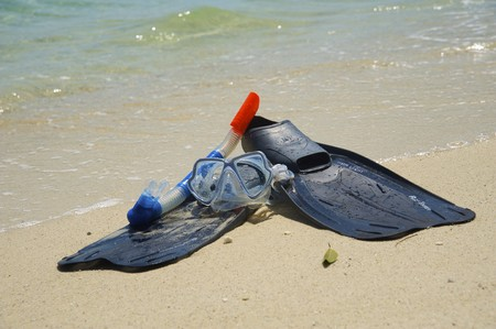 Snorkeling equipment (mask, snorkel and fins) on white sand beach with ocean on background photo