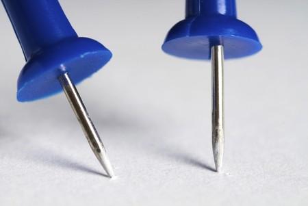 closeups: Blue push pin on a white background