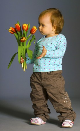 Small girl with the tulips in the studio photo