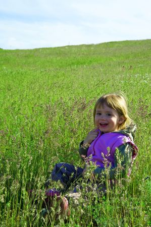 The little girl plays to a fresh grass photo