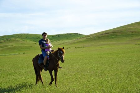 The little girl with the daddy go for a drive on a horse in steppe Stock Photo - 4934286