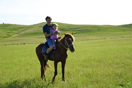 The little girl with the daddy go for a drive on a horse in steppe Stock Photo