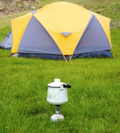 Camp kettle on gas stove with tent in background photo