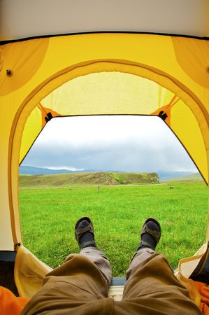 Man lying in tent with a view of mountain Stock Photo