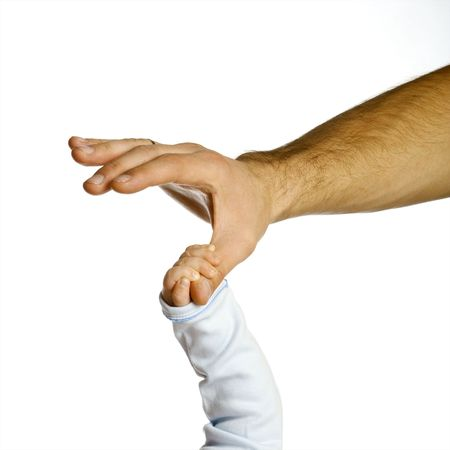 A childs hand holding an adults finger
