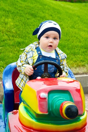 Happy boy driving toy vehicle in the amusement park. Stock Photo